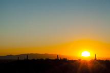 sun setting in a desert