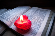 A pink heart-shaped lit candle sits upon an open bible