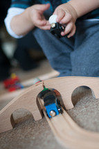 toddler playing with a wooden train