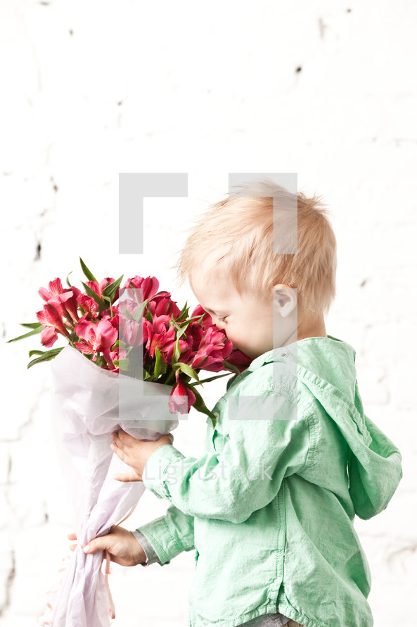 Boy smelling bouquet of flowers,