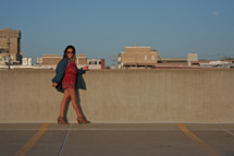 a woman walking at the top of a parking garage