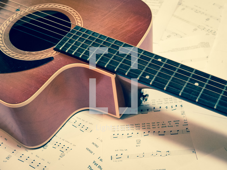 Guitar laying on sheets of music.