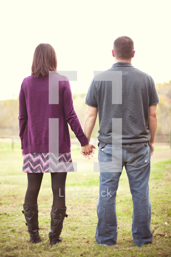 Couple standing in a pasture holding hands.
