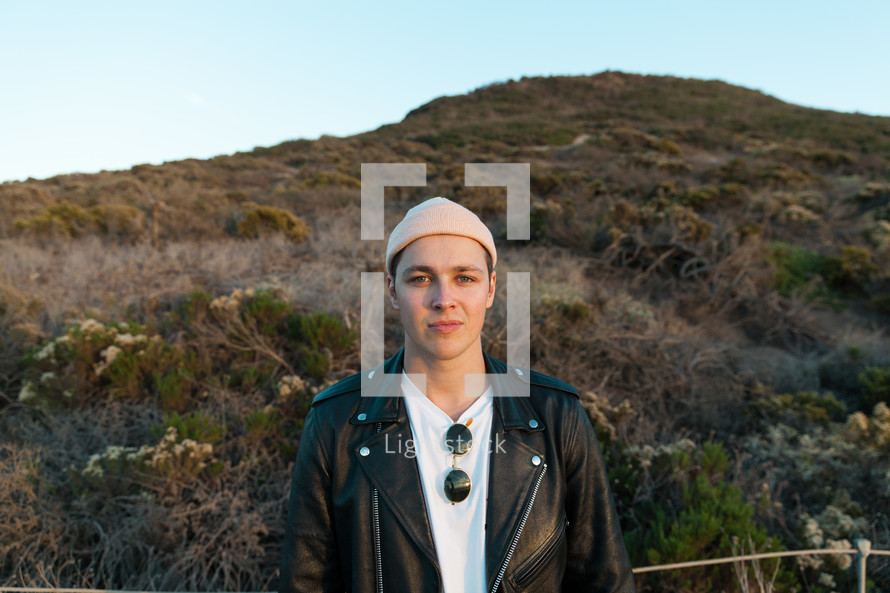 man in a beanie and leather jacket standing on a hill