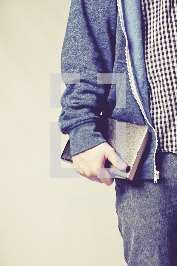 man carrying a Bible at his side