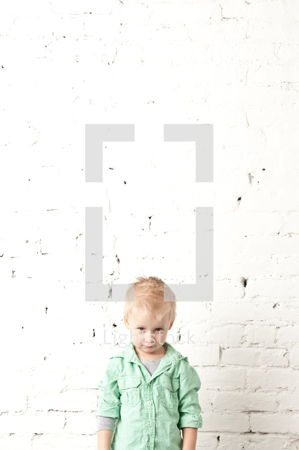 Boy standing in front of a brick wall.