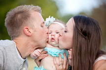 Couple kissing infant on the cheeks.