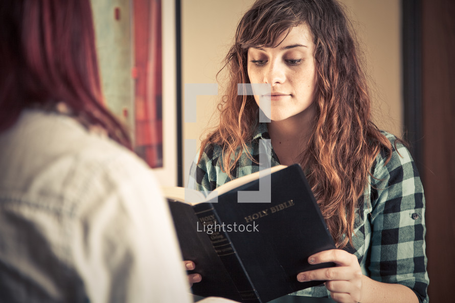 young women reading and discussing a Bible at a Bible study