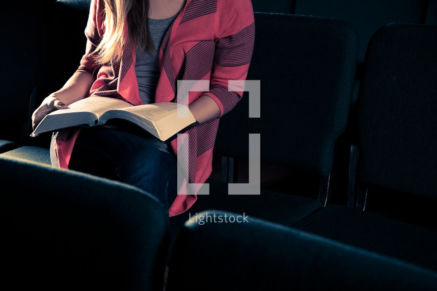 woman sitting in an empty church reading a Bible