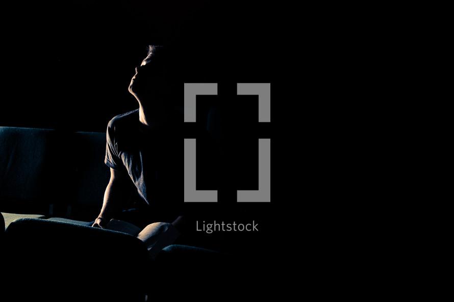 man sitting in a dark empty church looking up towards God