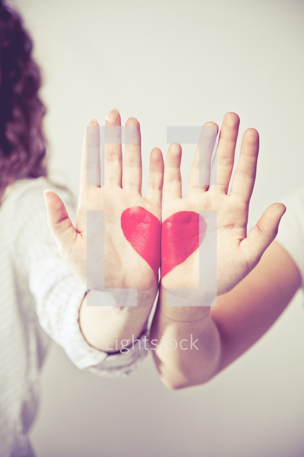 heart painted on the palms of hands