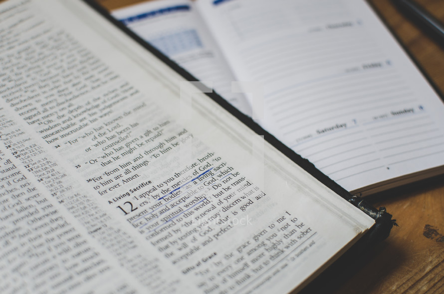 a bible open at Romans 12 on a desk next to a planner diary