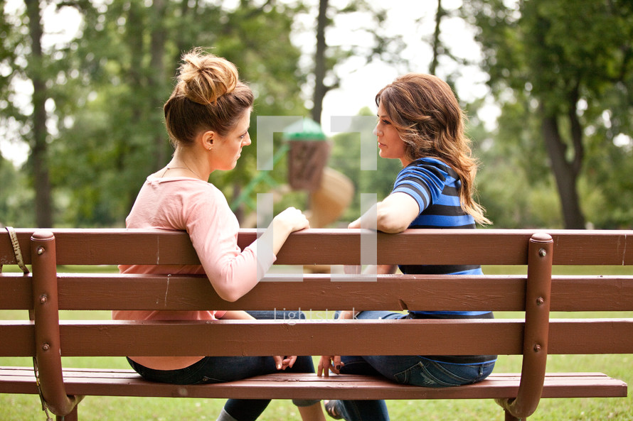 women in conversation on a park bench
