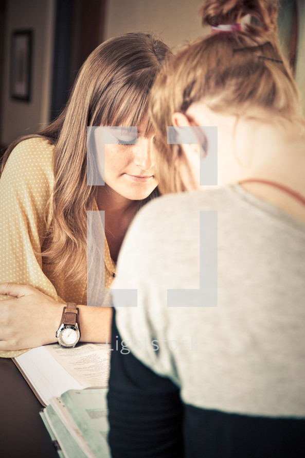 two young women reading Bibles at a Bible study