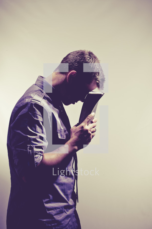 man in prayer with his head against the pages of a Bible