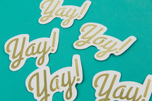 "Paper cutouts with the word ""yay!"" on an aqua background."