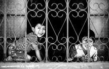 Boys playing behind chain window/fence