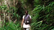 a woman hiking through a jungle