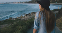 woman in a hat looking out at a beach