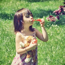 Girl holding stuffed animal while blowing bubbles outdoors.