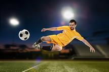 Man kicking a soccer ball on a soccer field