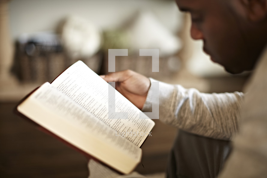 An African American man reads the Bible during his quiet time.