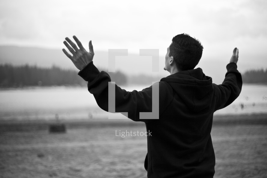 man with hands raised in praise and worship to God
