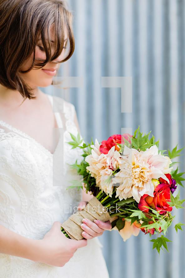 A bride holding a wedding bride bouquet burlap white dress