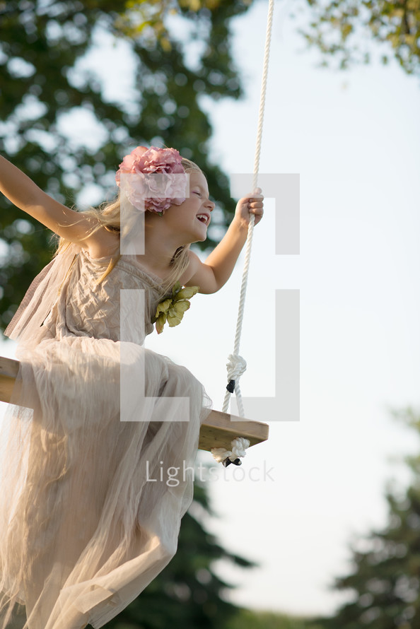 A young girl in a white dress swinging