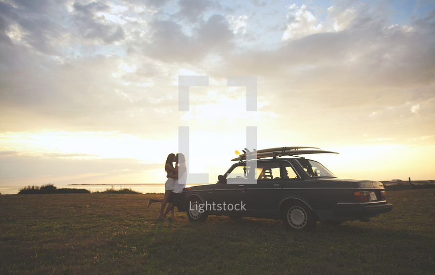 couple kissing leaning against a car with surf boards on top