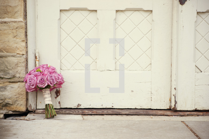 bouquet of pink roses resting by church doors