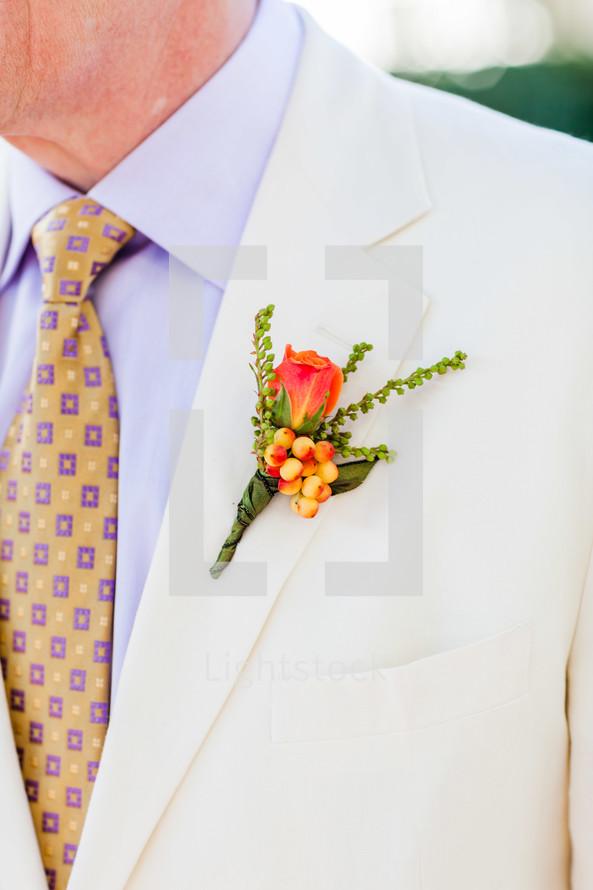 mens orange floral on a lapel white suit yellow tie