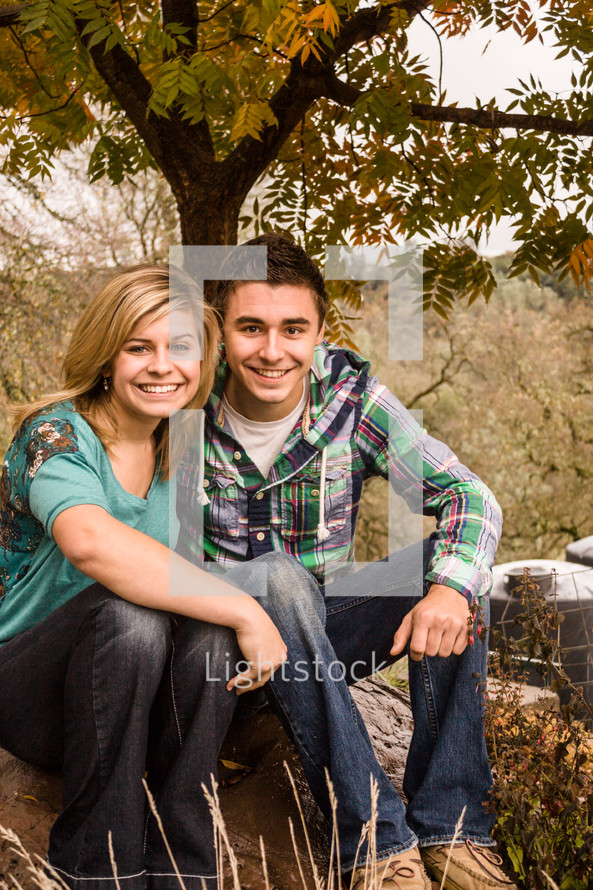couple sitting beneath a tree