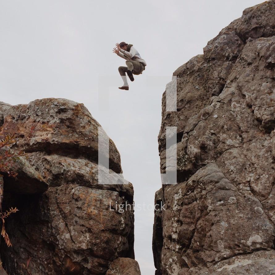 man leaping across a steep ravine