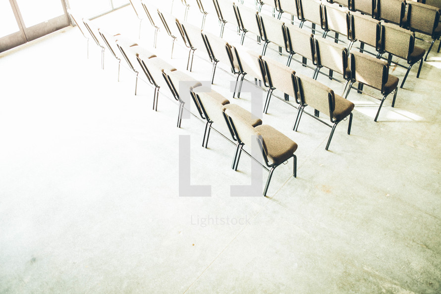light shining on empty rows of chairs in a church