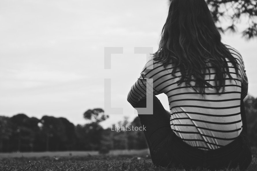 Back of girl sitting in field by tree looking into distance.