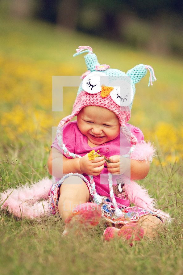 toddler girl sitting in the grass wearing an owl knit hat