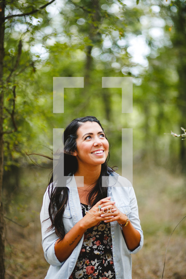woman with laced fingers standing outdoors looking to God