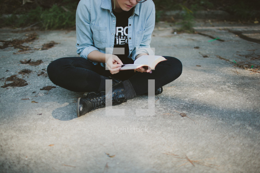 Teen reading Bible outdoors