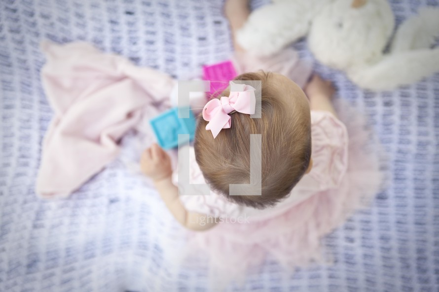 Infant baby girl playing on blanket