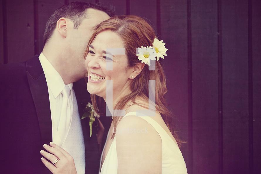 Groom kissing his smiling bride on the cheek