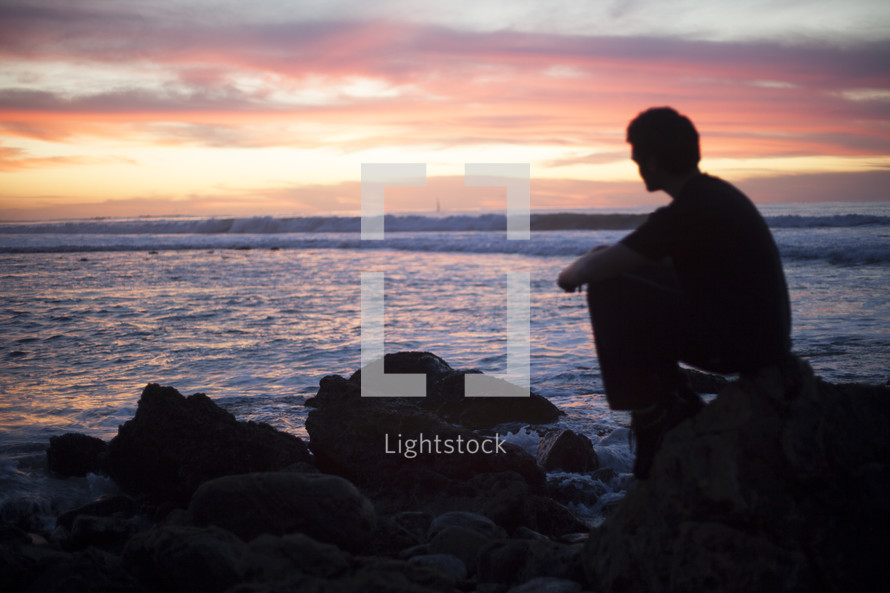man sitting on rocks by the ocean