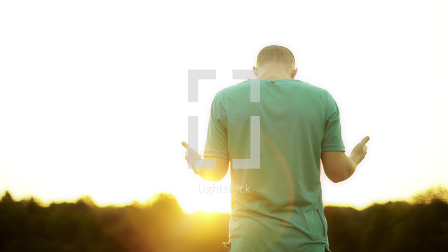 Young adult man worshipping at sunrise.