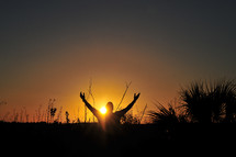 man with Hands Raised to the Lord at Sunset