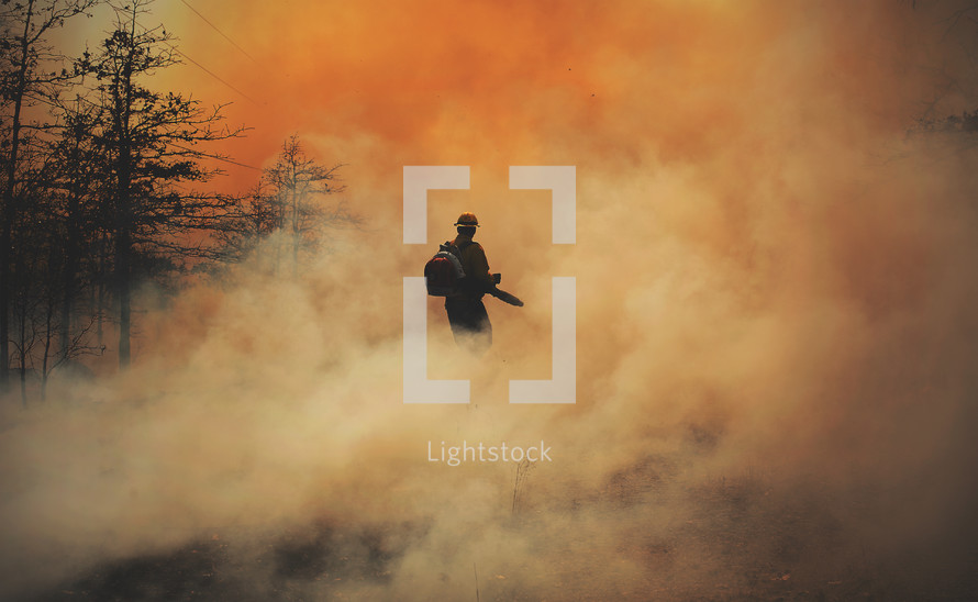 smoke building as fireman is putting out a forest fire