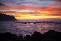 sunset over the sea on a rocky coastline