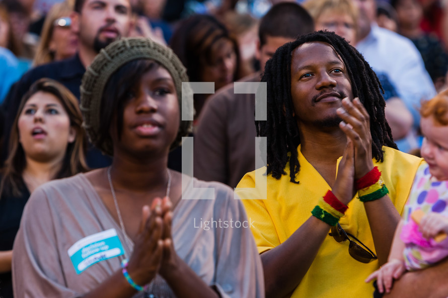 Black man and woman in church service clapping hands in praise and worship service