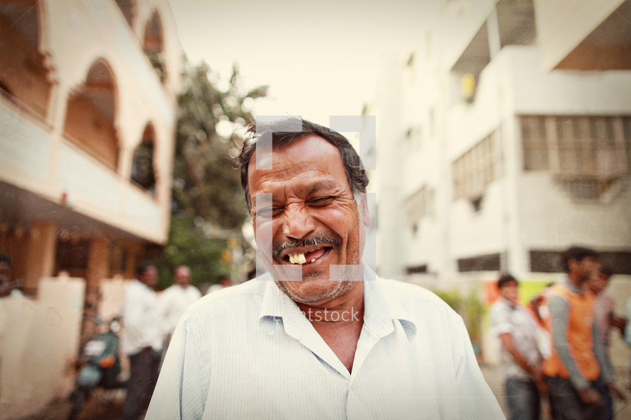 man in India smiling standing in a city alley