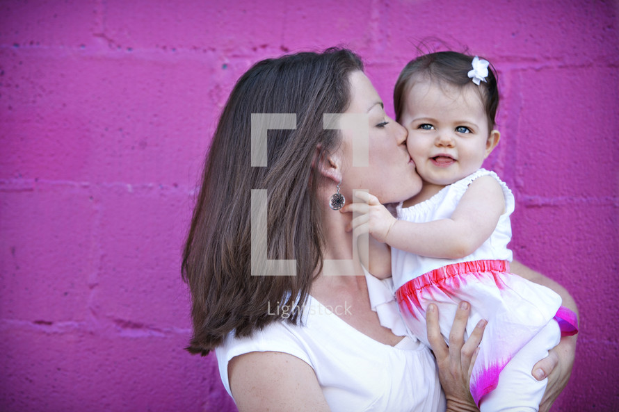 mother kissing her infant daughter's cheek