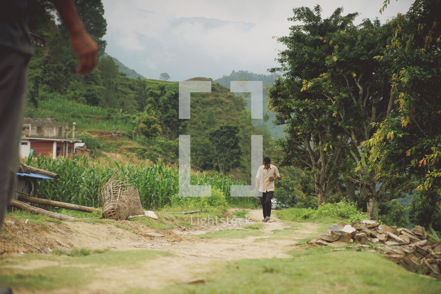 man walking down a dirt road into a village